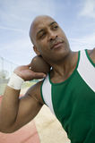 Male Athlete Ready To Throw Shot Put. African American male athlete ready to throw shot put on track and field Royalty Free Stock Image