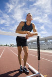 Male athlete resting arms on hurdle, low angle view Stock Image