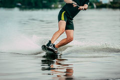 Male athlete rides on a wakeboard. On lake in summer Stock Image