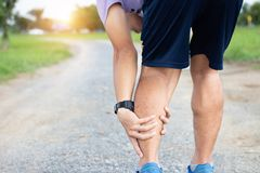 Male athlete runner muscle and ankle injury after jogging. Athlete man runner touching muscle in painful. Muscle and ankle injury. Concept royalty free stock image