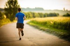 Male athlete/runner running on road Stock Photos