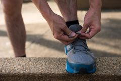 Male athlete Runner tying running shoes. Or shoelace on footpath with sunset light and getting ready for run. Healthy lifestyle for teenager, middle age worker royalty free stock photography