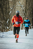 Male athlete running down a snowy alley in forest Stock Images