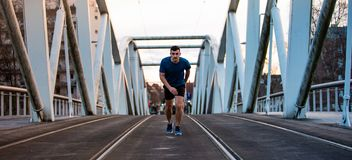 Male athlete running over sunset background royalty free stock photos