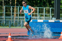 Male athlete running the steeplechase. Chelyabinsk, Russia - July 24, 2015: male athlete running the steeplechase during National competitions in memory of G. I Royalty Free Stock Photo
