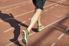 Male athlete running on track. Legs and shadow of a male athlete running on track Stock Image