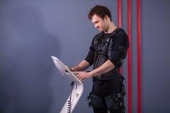 Athlete regulating intensity of ems electro muscular stimulation machine Royalty Free Stock Images