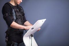 Athlete regulating intensity of ems electro muscular stimulation machine Royalty Free Stock Image