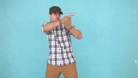 Male athlete of the shooter with the gun and glasses, aiming. Portrait of male athlete of the shooter with the gun and glasses, aiming isolate on blue background stock footage