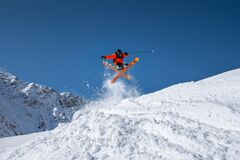 Free Male Athlete Skier In An Orange Trigger Makes A Jump Trick With Flying Snow Powder Against The Backdrop Of Snow-capped Stock Image - 179832861