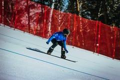 Male athlete snowboarder rides down mountain Stock Image
