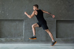 Male athlete sprinter running, exercising indoors Royalty Free Stock Images