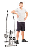 Male athlete standing next to a cross trainer machine. Full length portrait of a male athlete standing next to a cross trainer machine  on white background Stock Images