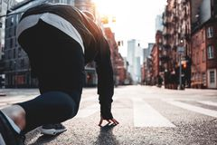 Young sporty man prepearing to start on urban running through on New York streets. Male athlete in start pose on city street. Young sporty man prepearing to stock photo