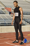 Male Athlete At Starting Block. Full length of confident male athlete at starting block in stadium Royalty Free Stock Image