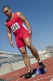 Male Athlete At Starting Line On Racetrack. Full length of mature male athlete at starting line on racetrack Royalty Free Stock Image