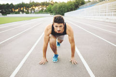 Male athlete on starting position. At athletics running track Royalty Free Stock Photos
