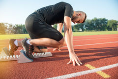 Male athlete on starting position at athletics running track. Royalty Free Stock Images