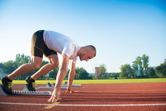 Male athlete on starting position at athletics running track. Stock Image