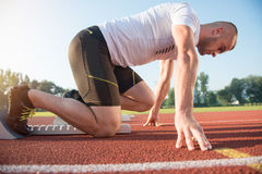 Male athlete on starting position at athletics running track. Royalty Free Stock Image
