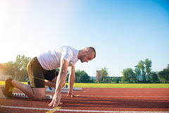 Male athlete on starting position at athletics running track. Royalty Free Stock Photography
