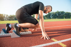 Male athlete on starting position at athletics running track. Royalty Free Stock Photos