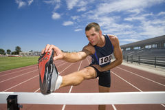Male athlete stretching hamstrings, foot on hurdle, low angle view Royalty Free Stock Image