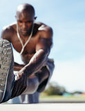 Male athlete stretching his leg muscles. With focus on leg. Muscular young man exercising outdoors Stock Photos