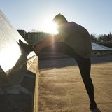 Male athlete stretching leg. With sunset behind, Montreal, Quebec, Canada Royalty Free Stock Photos