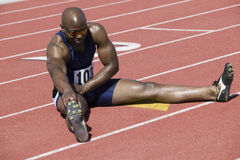Male Athlete Stretching On Racetrack. Full length of African American male athlete stretching on racetrack Stock Photos