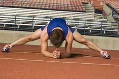 Male Athlete Stretching In Stadium. Full length of male athlete stretching legs in stadium Royalty Free Stock Photos