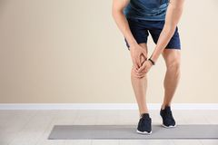 Male athlete suffering from knee pain during training. Indoors Royalty Free Stock Photos