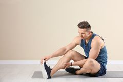 Male athlete suffering from leg pain during training. Indoors Royalty Free Stock Photography