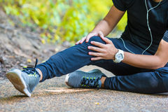 Male athlete suffering from pain in leg while Stock Image