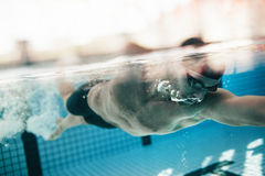 Male athlete swimming in pool. Underwater shot of male athlete swimming in pool. Young man swimming the front crawl in a pool Stock Photography