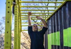 Male athlete swinging on monkey bars royalty free stock photography