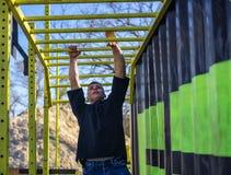 Male athlete swinging on monkey bars stock photography