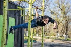 Male athlete swinging on monkey bars stock images