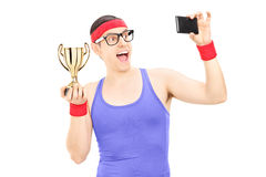 Male athlete taking a selfie holding a trophy Royalty Free Stock Photo