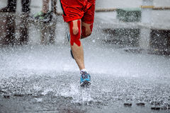 Male athlete with tape on his knees running. Through a puddle of water, splashes and drops around feet Royalty Free Stock Photo