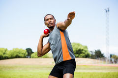 Male athlete about to throw shot put ball. In stadium Stock Photo