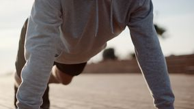 Sportsman is doing pushups on street during morning work out stock video footage
