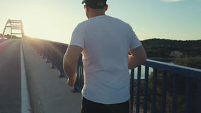 Male athlete training alone. Male athlete training alone, running on the bridge in Croatia Royalty Free Stock Photography