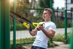 A male athlete goes in for sports in the open air. Muscular arms. Blonde in a white T-shirt. Lifestyle of the. A male athlete trains on hinges, in a city in Royalty Free Stock Photography