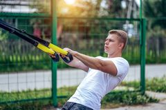 A male athlete goes in for sports in the open air. Muscular arms. Blonde in a white T-shirt. Lifestyle of the. A male athlete trains hinges, in a city in the Stock Image