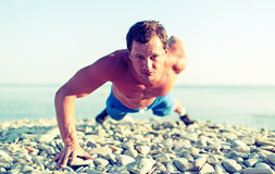 Male athlete trains pushed on nature on the beach Stock Photography