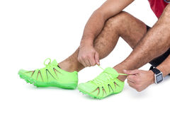 Male athlete tying his running shoes. On white background Stock Photography