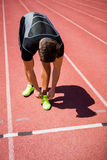 Male athlete tying his shoe laces on running track Stock Photos
