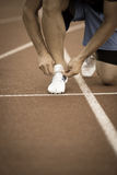 Male athlete tying laces for jogging. Man jogging on a running track. Stock Photos