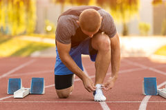 Male athlete tying laces for jogging. Man jogging on a running track. running shoes. Fitness health Royalty Free Stock Image